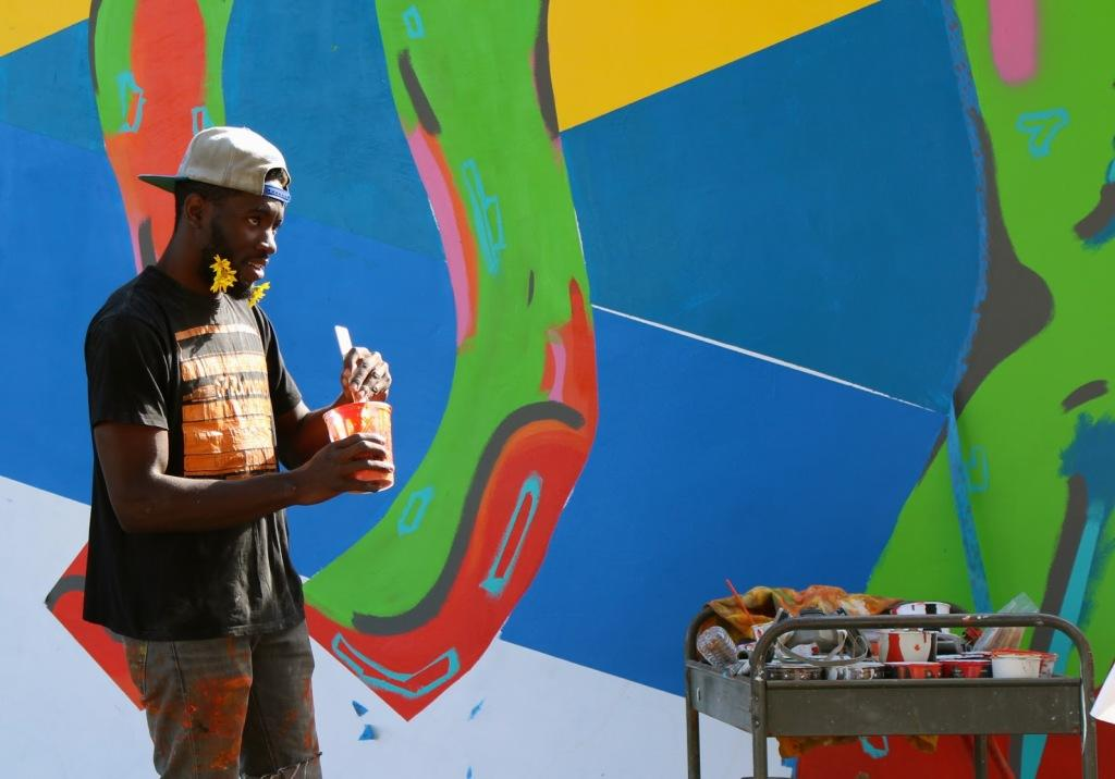 Josiah+Ihem%2C+23%2C+a+fine+arts+major%2C+paints+a+mural+on+the+wall+facing+Alumni+Park+on+Oct.+22.+He+is+one+of+a+few+students+who+have+created+art+around+campus.+The+mural+represents+various+majors+to+show+how+they+interact+with+each+other.%0APhoto+by+Diana+Olivares%2FThe+Runner