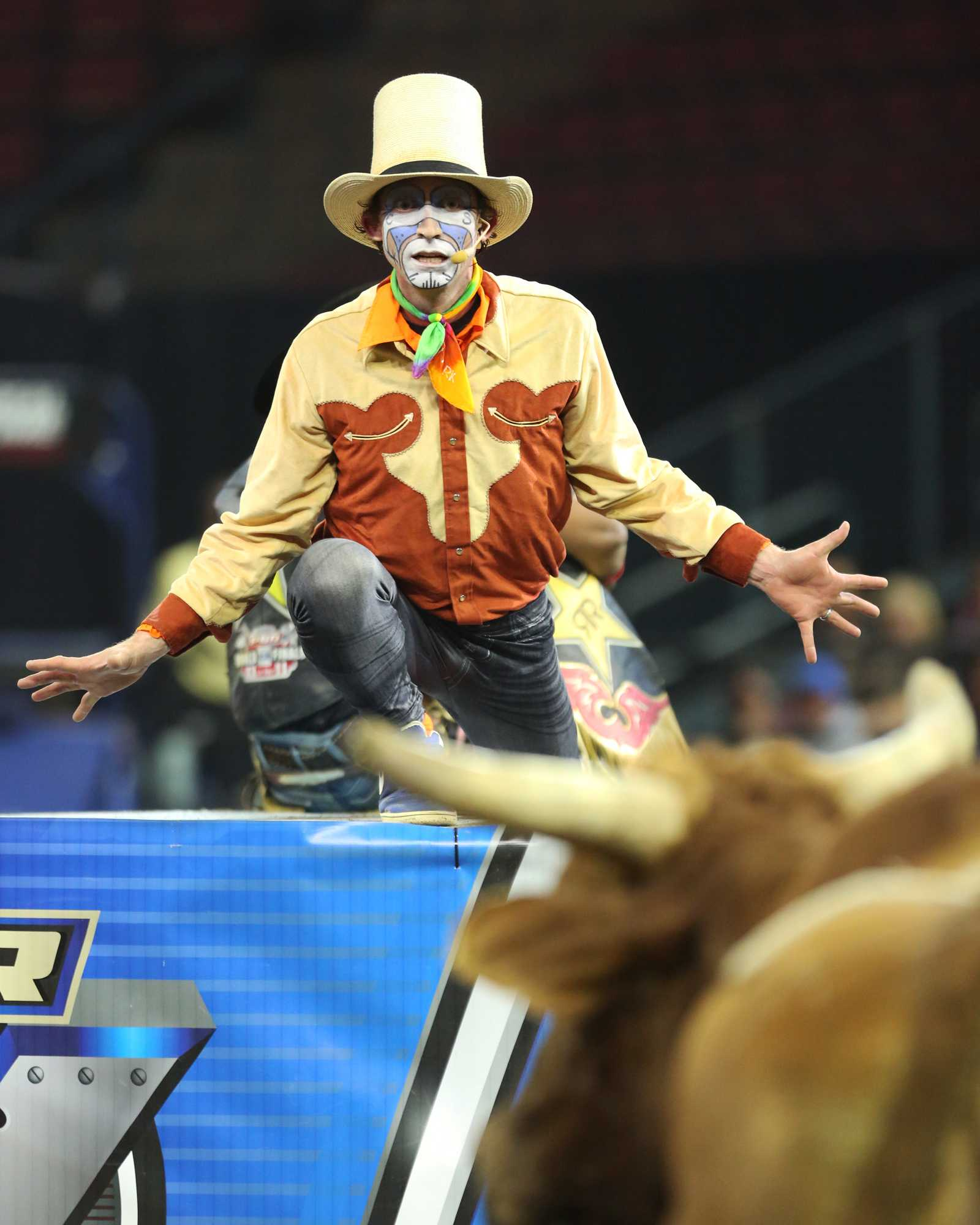 The entertainer for the night taunts the bull as he stands in the center cage of for safety.