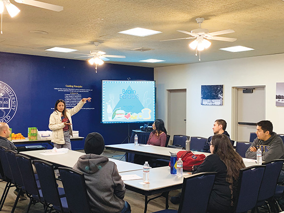 Andrew Paredez/The Runner/  Luz Zamudio-Torres, a Dignity Health Community Wellness Specialist, spoke to students on December 3, 2018 about the changes students can make to their diets at a more affordable price.