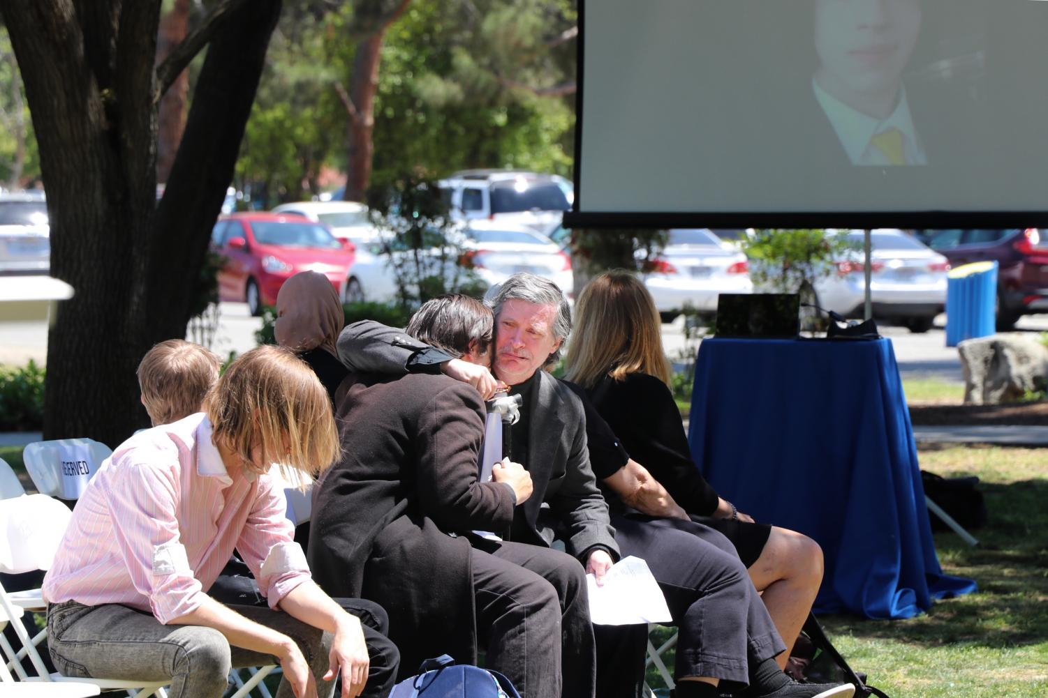 Leviak Kelly, father to Jason Quinn Kelly, comforted his son Andrew Kelly during a brief stream of pictures and videos in Quinn's memory, near the conclusion of Quinn's memorial service at CSU Bakersfield on April 24.  Sergio Hernandez/The Runner