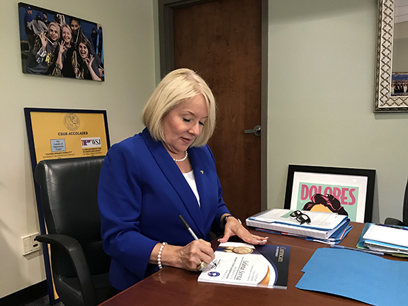 CSUB President, Lynnette Zelezny, signing student achievement certificates in her office on April 30, 2019.