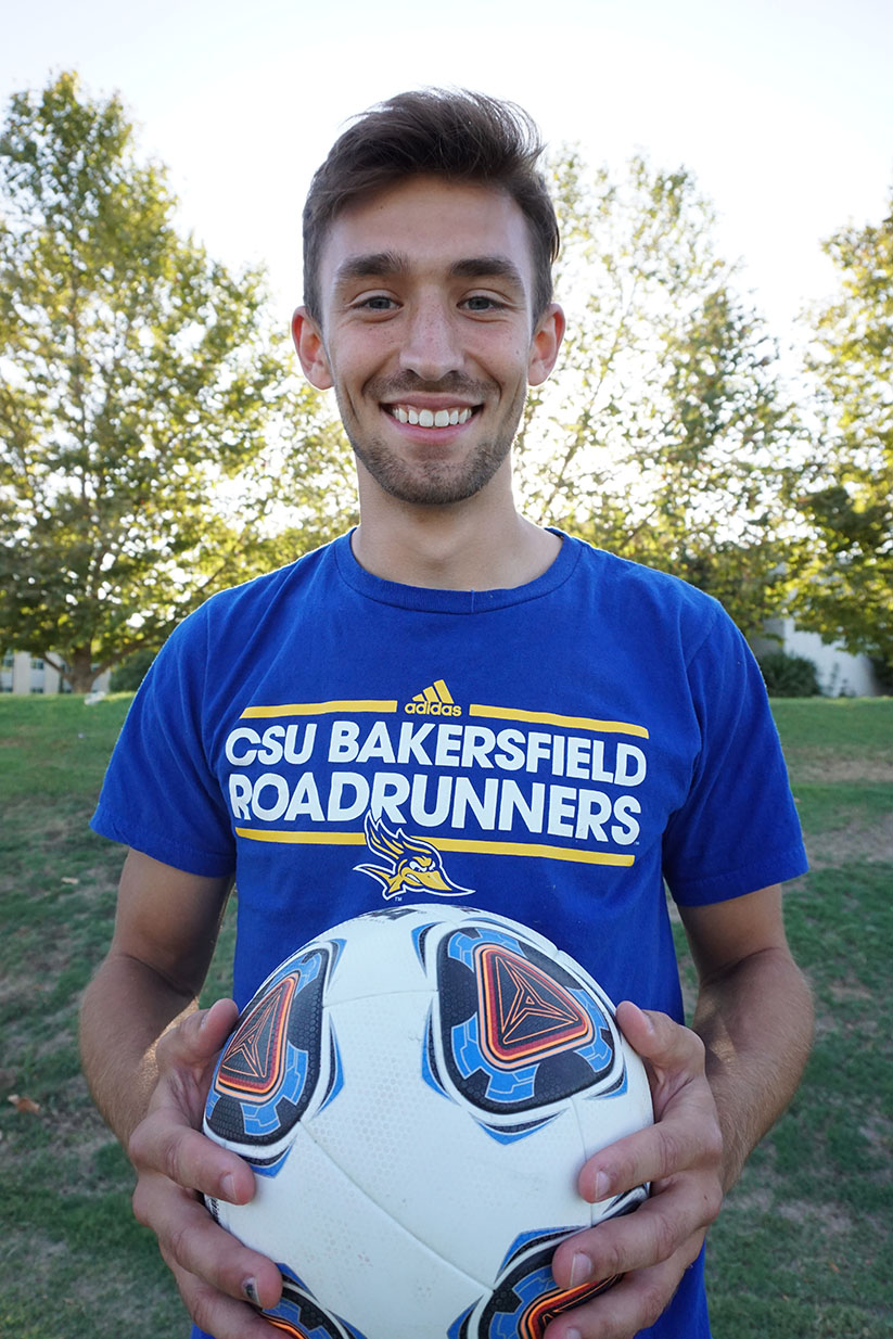 Niklas Körber, senior forward for men's soccer team poses with ball after being named Athlete of the Week by The Runner.