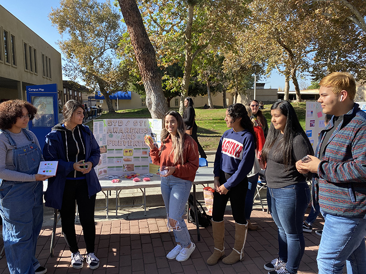 Students+gather+around+their+%22STD%2FSTI+Awareness+and+Prevention%22+poster+to+bring+awareness+to+safe+practices+to+the+students+on+campus.+