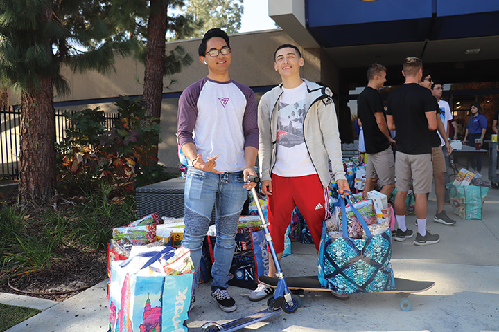 Jorge+Moreno+%28right%29+and+Trent+Cardenas+%28left%29%2C+were+a+few+of+many+students+who+participated+in+the+food+distribution+at+the+stockdale+court+on+Nov.+18%2C+2019.